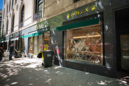 CHICAGO, ILLINOIS - MAY 31, 2019: Broken store windows as act of vandalism on Michigan avenue in Chicago. Rolex store after after nights of riots and chaos 에디토리얼