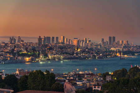 Istanbul waterfront cityscape with modern buildings and boats at sunset, Turkey