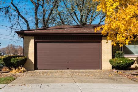 Brick car garage with old brown door. Multicolor trees in autumn