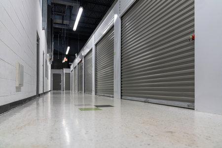 Storage warehouse interior. Metal garage doors with locks. Low angle shot