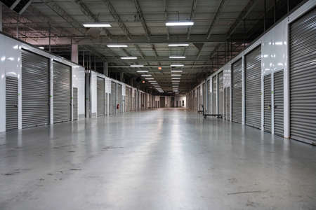 Wide corridor in Storage facility with gray doors. Moving, storage concept. 版權商用圖片