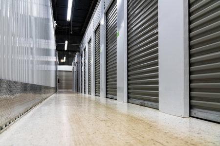 Storage warehouse interior. Metal garage doors with locks. Low angle view