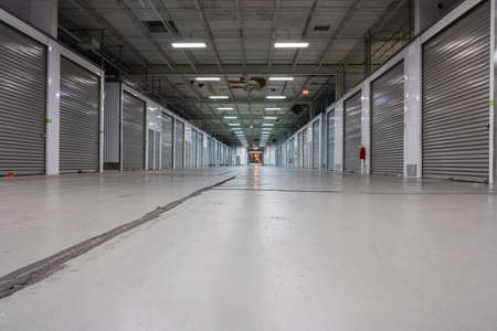 Large Storage warehouse corridor interior. Metal garage doors with locks. Low angle shot Foto de archivo