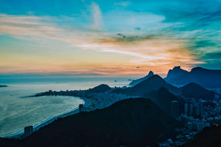 Wide angle view of Rio de Janeiro with Copacabana Beach and mountains aroud the city at sunset