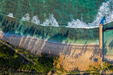 Aerial view of Waikiki Queens Beach, Oahu. Famous surfers beach. Morning light with long palm shadows.