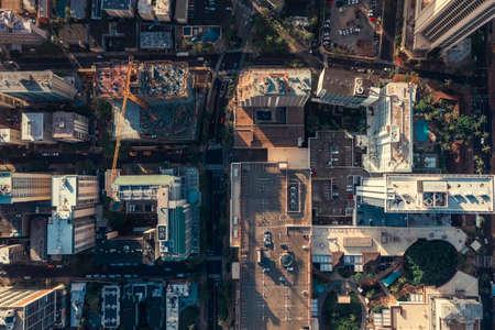 Aerial top down view of main street in downtown Waikiki, Honolulu. Urban construction area, Oahu Island