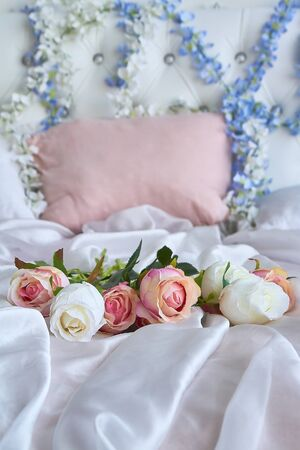 A bouquet of artificial flowers lies on a white silk blanket on a large bed
