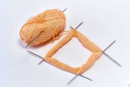 knitting needles and pink yarn with white copyspace 写真素材