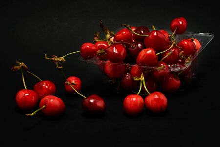 Container of fresh cherries on a black background