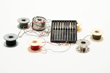 Set of needles and threads for a sewing machine on a white background