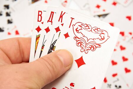 Playing cards in hands on a background of scattered cards 写真素材