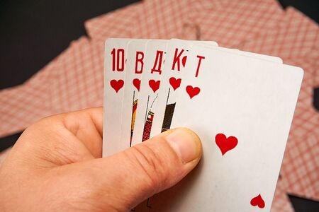 Playing cards in hands on a background of scattered inverted cards