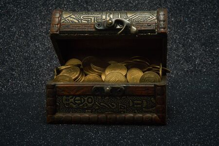 A chest with coins on a dark background