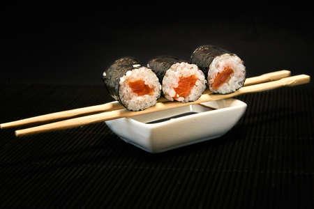 Three pieces of syake maki roll lying on sticks on a black background