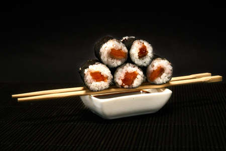 Shiake Maki roll lies on sticks on a black background