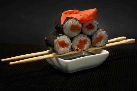 Shiake Maki roll lies on sticks, covered with ginger on a black background