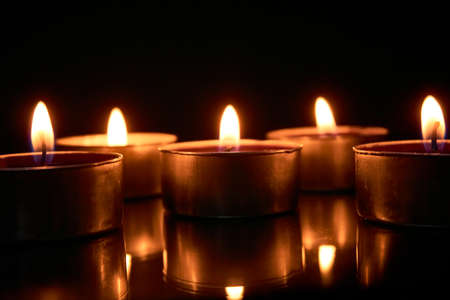 Burning candles on a black background, selective focus, romantic setting, romantic atmosphere, shot with shallow depth of field