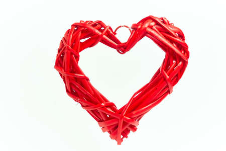 Red wicker heart made of handmade tree branches on a white background. A holiday of love. Valentine's day