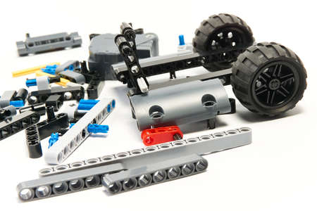 Plastic parts of the constructor, connecting elements and wheels for assembling movable models on a white background, floating focus Reklamní fotografie