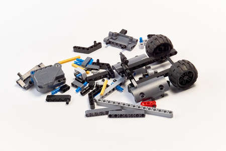 Plastic parts of the constructor, connecting elements and wheels for assembling movable models on a white background, floating focus