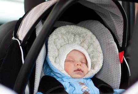 newborn boy sleeping in a car seat installed in the car photo