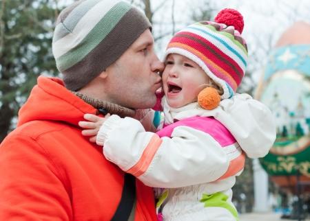 niño llorando: Papá y besos al aire libre alivia hija Foto de archivo