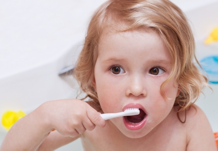 brush teeth: Cute baby have in the bathroom brushing her teeth with a toothbrush