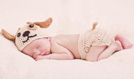knit cap: cute newborn baby sleeps in a knitted hat dogs Stock Photo