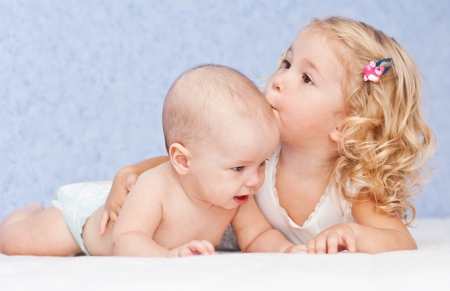 baby child: happy little girl hugging kissing his brother on a blue background