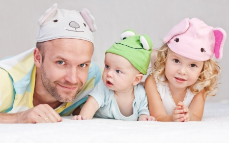 happy dad with kids in funny hats lying on the bed