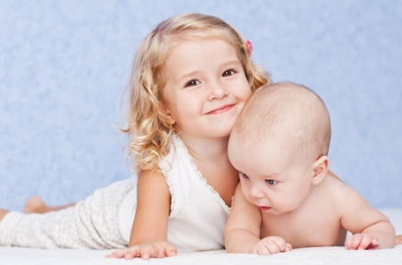 brothers: happy little sister hugging her brother lying  Stock Photo