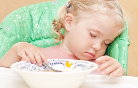 tenager: little girl fell asleep at the table eating soup with a spoon in his hand