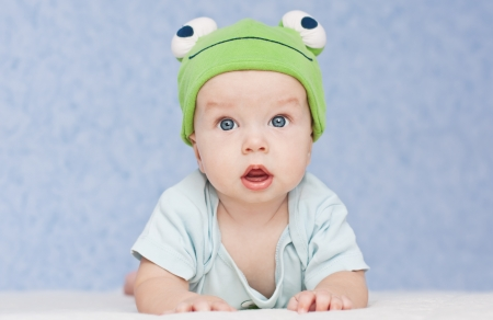 baby in the hat frog lying on his stomach photo