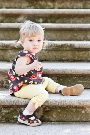 Little cute girl in sitting on the stairs with stone steps, selective focus on face Stock Photo