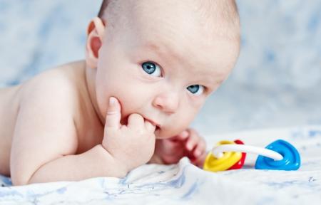 boca abierta: Beb� feliz lindo chuparse el dedo y tiene un sonajero Foto de archivo