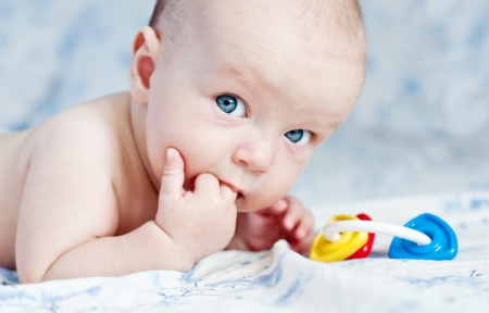Cute happy baby thumb-sucking and plays a rattle Standard-Bild