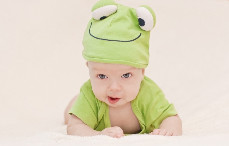baby in the hat frog lying on his stomach