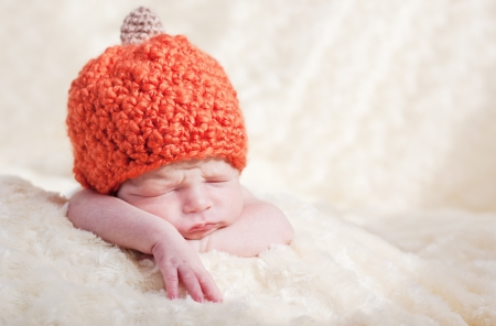 sweet sleeping baby with pumpkin hat photo