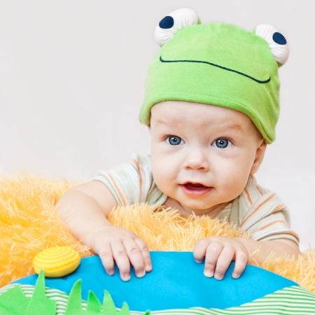 cute baby playing in the hat frog lying on his stomach on a white background photo