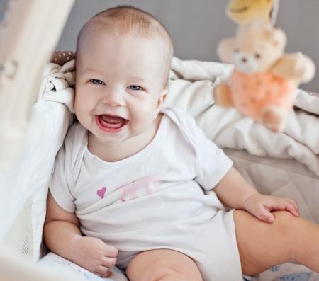 bebe sentado: beb� feliz sentado en la cama mirando a la c�mara