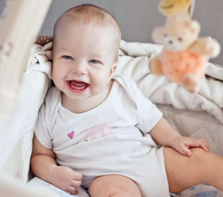 early childhood: happy baby sitting in bed looking at the camera Stock Photo