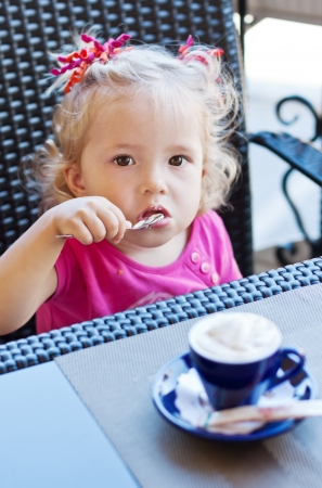 funny toddler girl in cafe looking at the camera photo