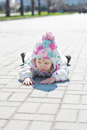 tripped:  little angry toddler girl  outdoors lying on the pavement