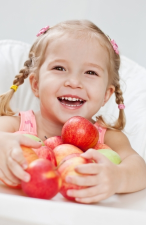 happy little girl with red apple while sitting at a table on a white background (soft focus) Standard-Bild