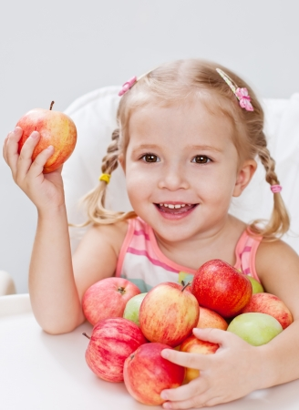 happy little girl with red apple while sitting at a table on a white background (soft focus) Stock Photo