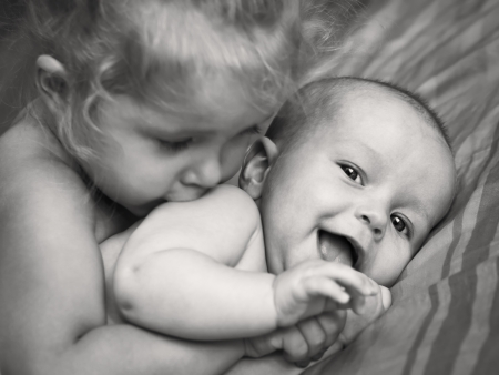 happy little girl hugging kissing his brother (black and white image) Standard-Bild