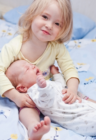 newborn brother at the hands of the little sister