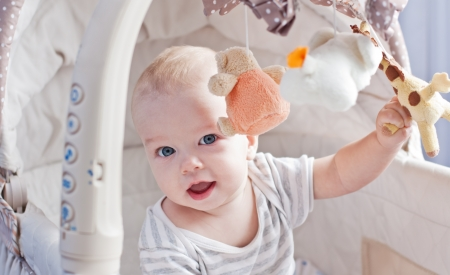 Baby boy playing sitting in the cradle with mobile toy giraffe