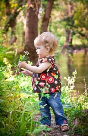 Cute baby girl with a flower on the river on a summer day photo
