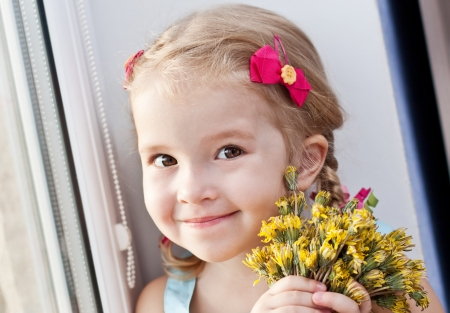 cute little girl with dandelion flowers smiling looking at the camera on a white background Stock Photo